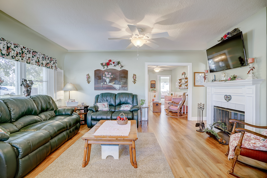 Alternate view of living room with built-in shelving and gorgeous original fireplace.