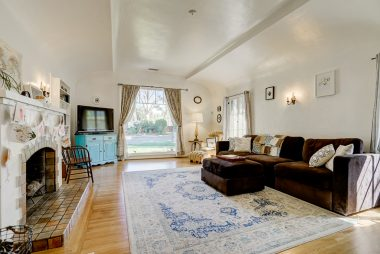 Separate living room with barrel ceiling, original fireplace, and large picture window which allows the natural light to cascade inward.