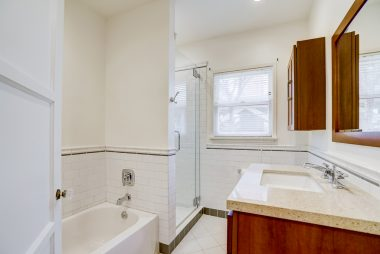 Remodeled bathroom with tub, newer glass-enclosed shower, and granite-covered vanity..