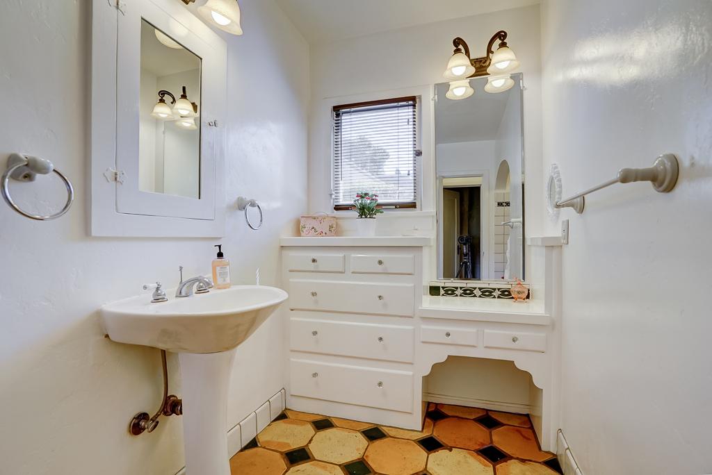 Hallway bathroom with original built-in cabinetry and makeup desk.