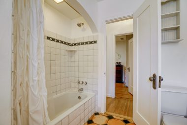 Shower-in-tub in hallway bathroom.