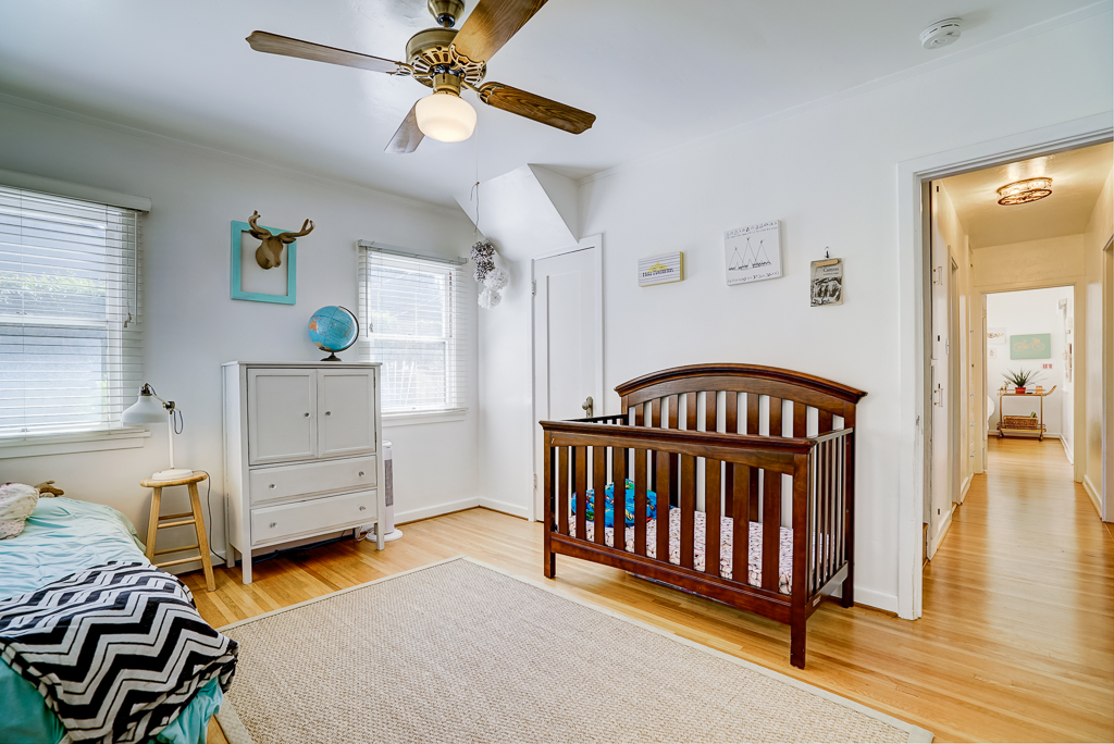 First of three downstairs bedroom, this overlooking the front of the house with hardwood flooring and ceiling fan.