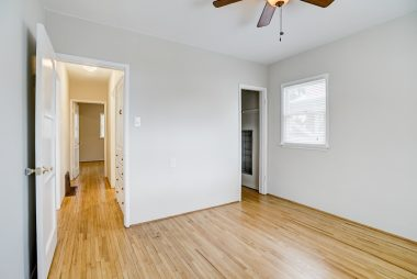 Both bedrooms boast gorgeous hardwood floors, while this bedroom has a ceiling fan and original built-in shoe holder in closet.
