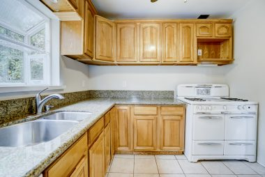 Remodeled kitchen with dishwasher, refrigerator, and antique stove.