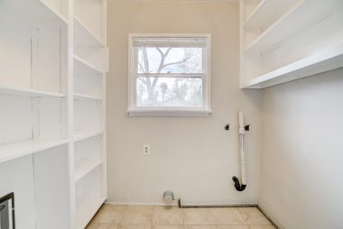 Indoor laundry room with pantry shelves and doggy (or kitty) door leading to the back porch.