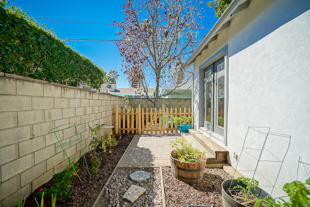 Side yard with privacy block wall and fence leading to back yard.