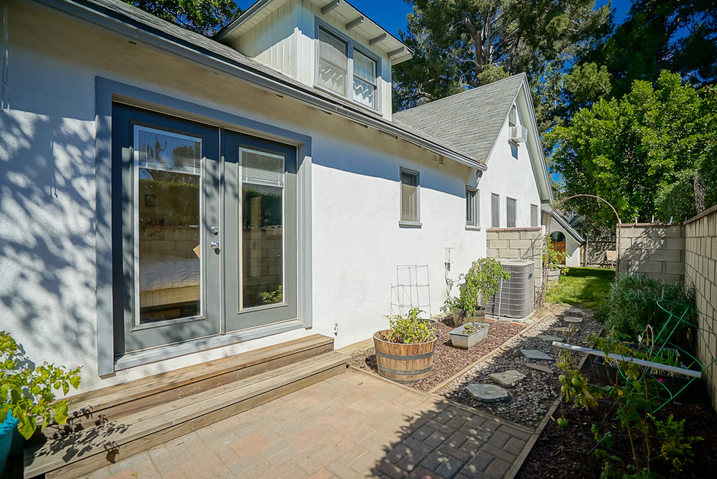 French doors off the master bedroom lead to the back yard and side yard with gardens.