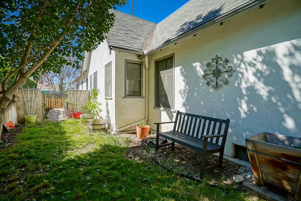 Side yard towards front of house with partial shade and grassy area for hanging out and and/or gardening.