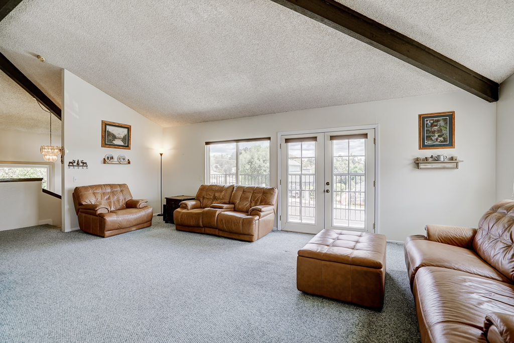 Super spacious living room with beamed ceiling overlooking the front yard, with French doors leading to a balcony with lovely views of Riverside.