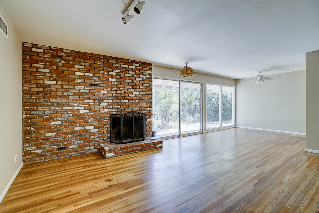 Brick Fireplace Refinished Hardwood Floors Track Lighting Ceiling Fan Over Dining Area