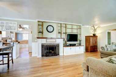 Spacious living room with wood-burning fireplace, custom shelving, crown molding and baseboards., and original oak hardwood flooring.