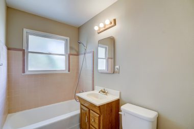 Hallway bathroom with soaking tub and fresh two-toned paint.