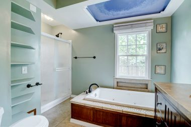 Remodeled hallway bathroom with spa tub and separate shower and newer vanity.