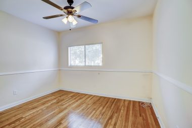 First of three bedrooms, with hardwood floors exposed, ceiling fan, and new window blinds.