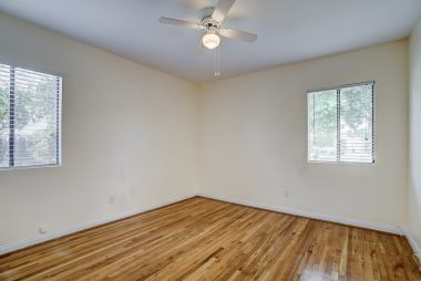 Second of three bedrooms, with exposed hardwood floors, ceiling fan, and new window blinds.