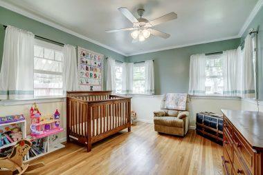 Front bedroom with original oak hardwood floors, newer dual pane energy-efficient vinyl windows, and ceiling fan.