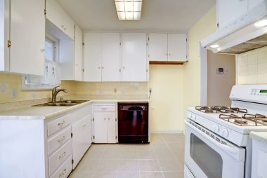 Charming kitchen with lots of cabinetry, dishwasher, gas stove, and tile flooring.