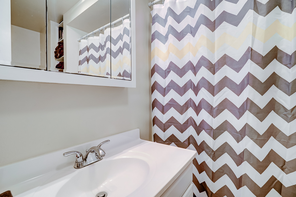 Full bathroom downstairs, with shower in tub and charming open linen shelves.