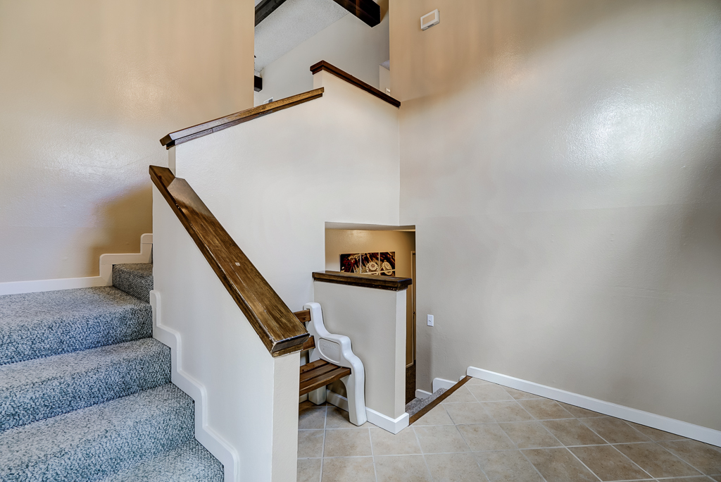Foyer with stairs leading to main floor of home, where living room, kitchen and 3 bedrooms/2 bathrooms are located.