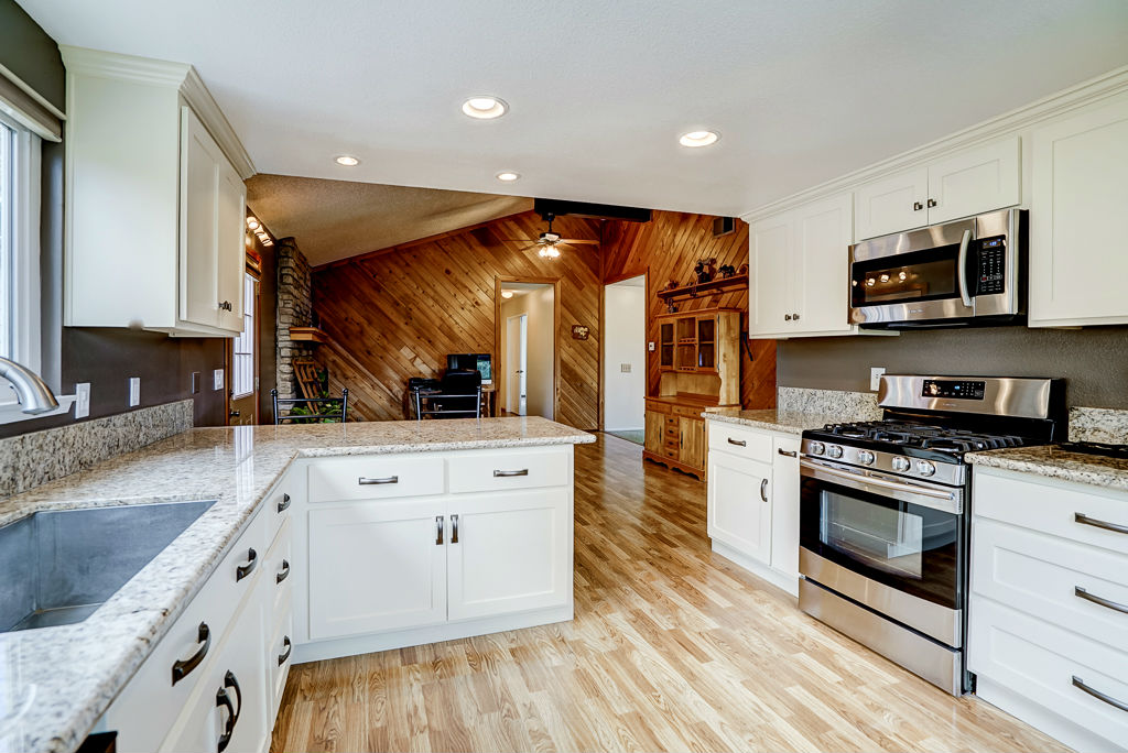 Alternate view of kitchen (space enough for a preparation island), looking towards the family room with fireplace.