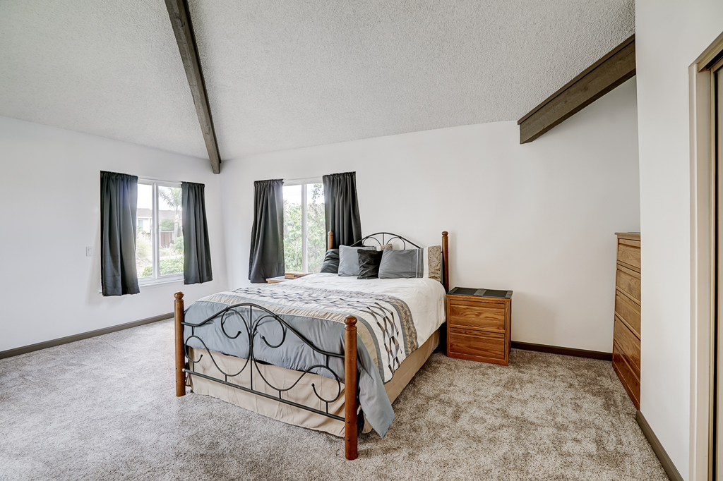 Expansive master bedroom with cathedral and beamed ceiling with walk-in closet and private remodeled bathroom.