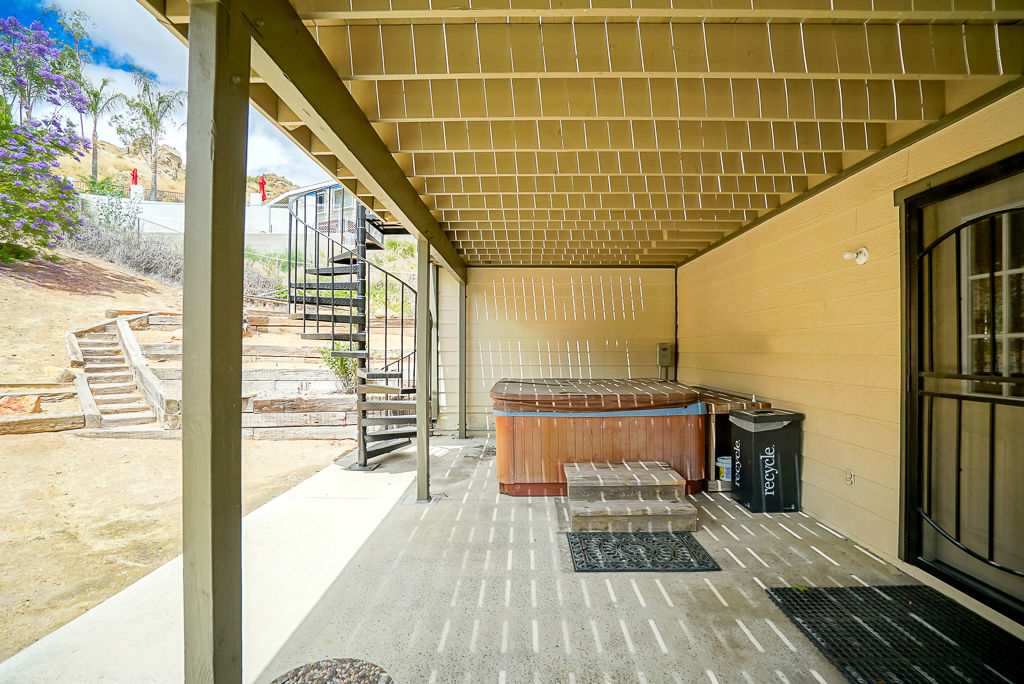 Patio outside downstairs bonus room with spa (included and works great) with spiral staircase leading to upper redwood deck which can also be accessed by the upstairs family room/kitchen area.