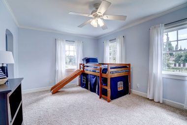 The fourth of four upstairs bedrooms with carpeting, ceiling fan, and a smaller walk-in closet.