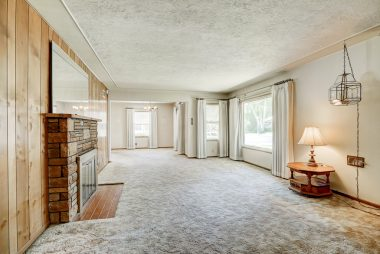 Living room with fireplace and hardwood floors under carpeting (look inside closet to see what the floors look like).