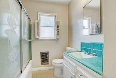 Bathroom with shower in tub, working original wall heater with newer toilet.