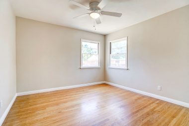 Back bedroom with hardwood floors and ceiling fan.