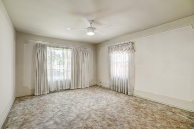 Spacious front bedroom with hardwood floors under carpeting.