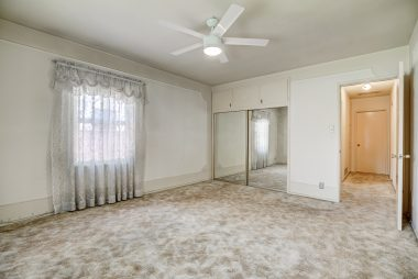 Alternate view of spacious front bedroom with mirrored wardrobe doors, cabinets above the closet, and ceiling fan.