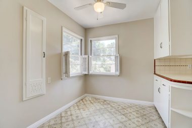 Cute little nook area with ceiling fan and corner windows with shutters.