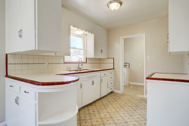 Original retro kitchen with built-in rounded shelving and tile counter tops and back splash.
