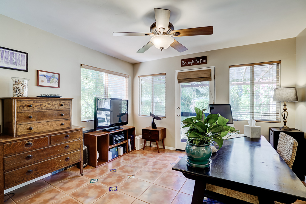 Family room with ceiling fan and doorway to back patio.