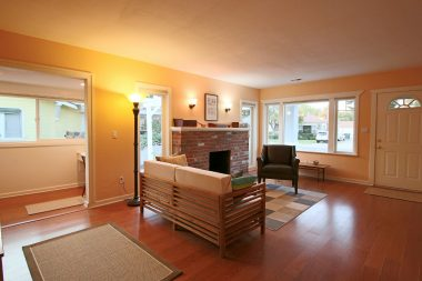 Living room with fireplace and lots of bright windows. Hunter Douglas cordless blinds on all windows!