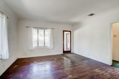 Front door entrance into living room with coved ceiling and original hardwood floors which need to be refinished.