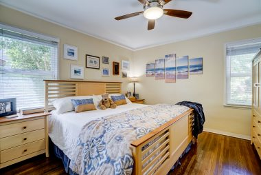 Back bedroom with gorgeous original hardwood floors, custom closet system, and new lifetime warranty ceiling fan which uses less electricity. This room swallows up this Eastern King bed.