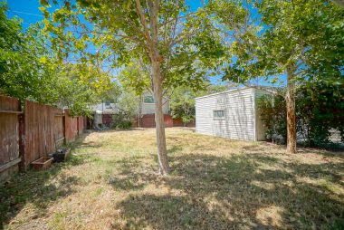 Spacious backyard large enough for pool and garden if desired, with mature shade trees.