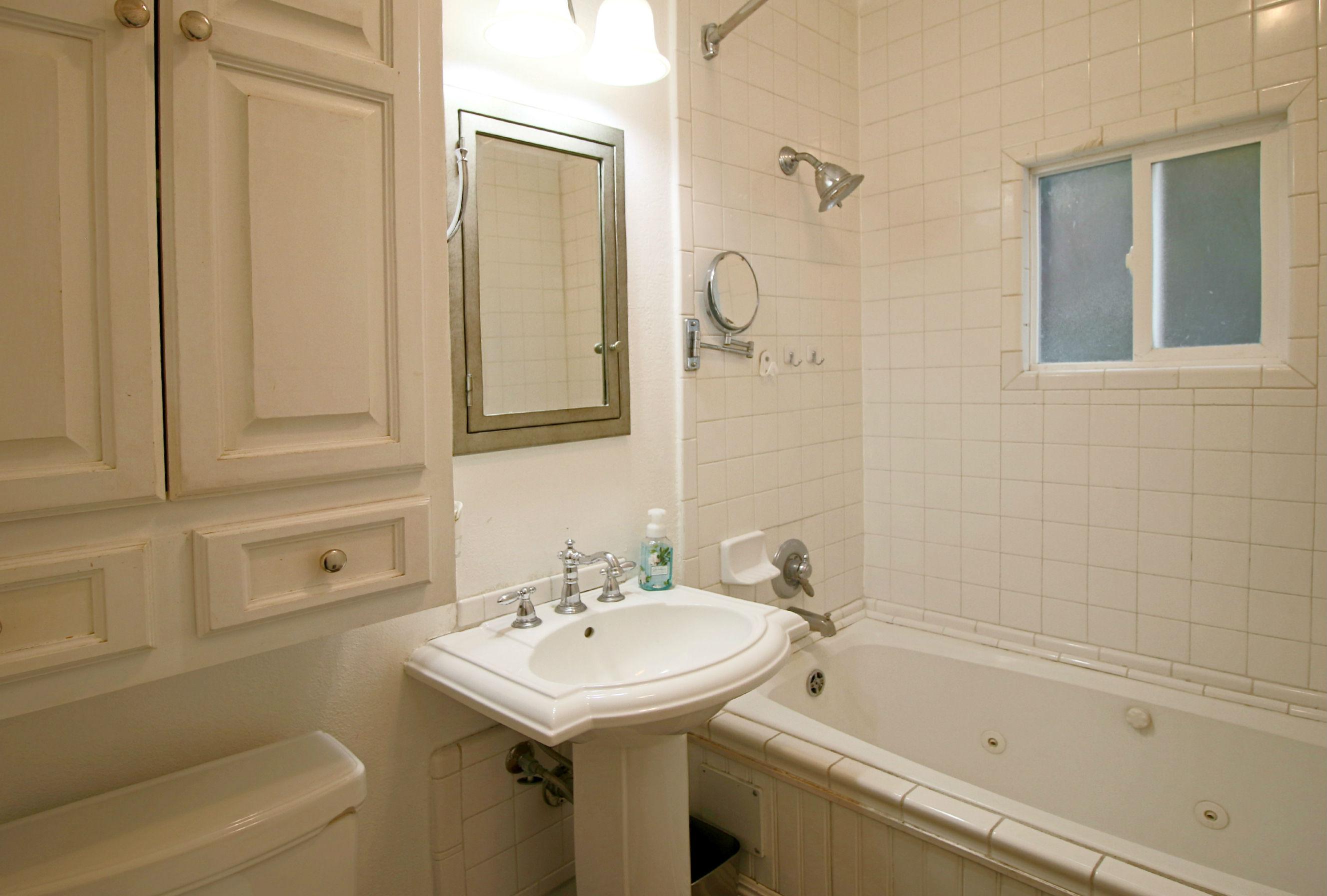 Hallway bathroom with spa tub and pedestal sink.