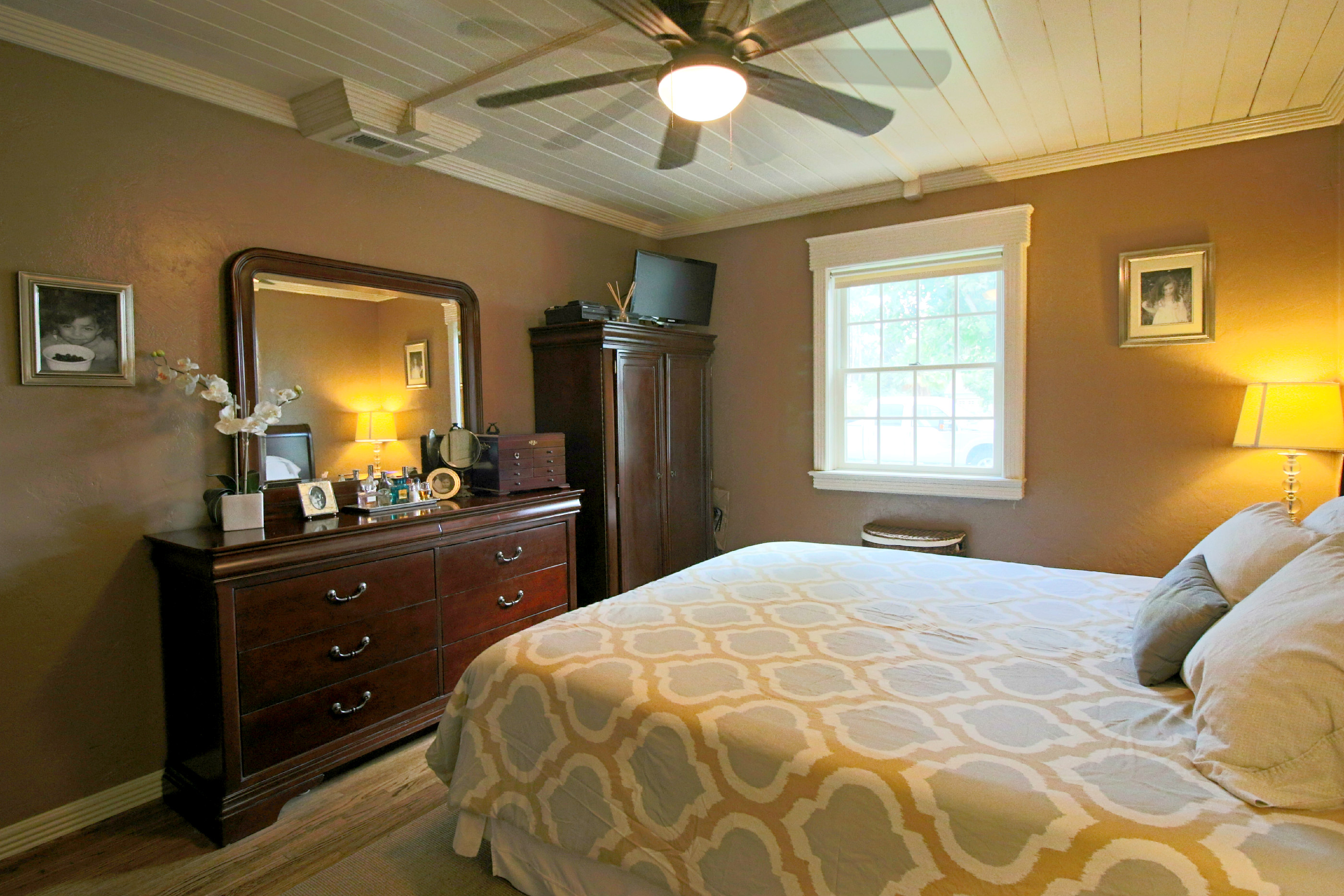 Master bedroom with ceiling fan, hardwood floors, and double pane windows.