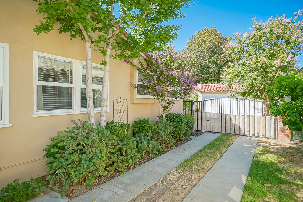 """""""Hollywood"""" driveway with electric wrought iron gate and a detached 2-car garage, plus RV parking in the back portion of the yard off the alley, with wiring for electric car station."""