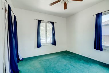 Front bedroom with hardwood floors under carpeting. This room has a separate entrance from the front porch, so would be ideal for guests, roommate, or college student.
