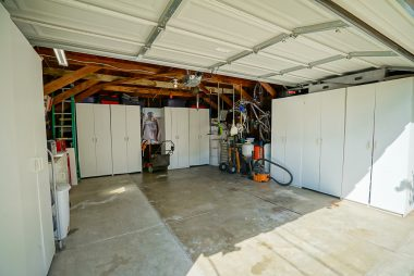 Detached 2-car garage with loads of storage cabinets.