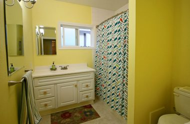 Full hallway bathroom with newer vanity, and shower in tub.