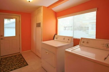 Indoor laundry (washer/dryer included) with new door with interior blinds.