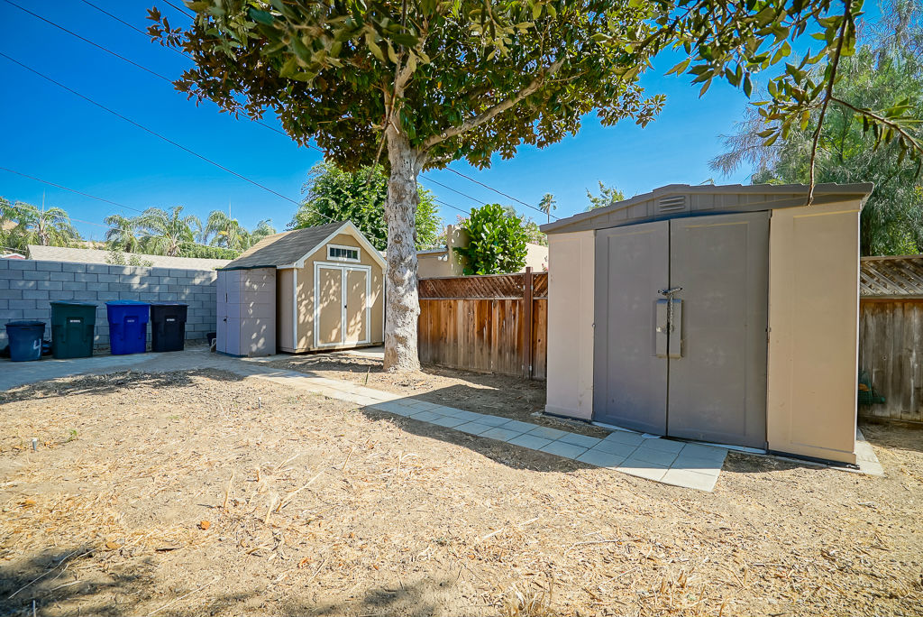 Fenced area behind the landscaped yard with room for garden, pool, and RV parking. Three sheds shall remain with the property.