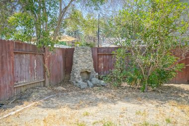 Far back corner of yard has what very likely could be an original outdoor fireplace.