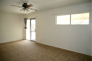 Back bedroom with newer carpeting and ceiling fan.