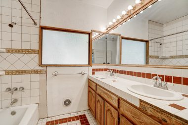 Hallway bathroom with double vanity.